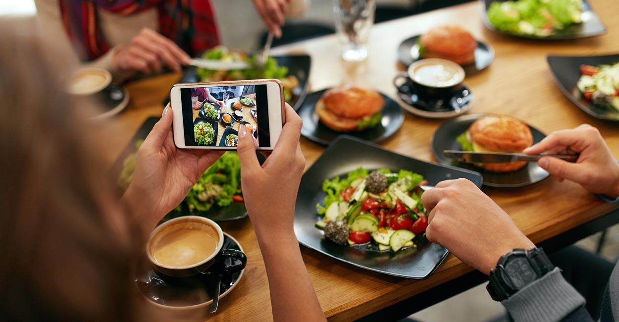 contenuti pagina facebook ristorante, persone fotografano cibo sul tavolo